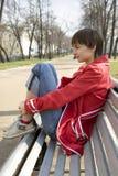 Retrato de la chica joven que se sienta en el banco Foto de archivo libre de regalías