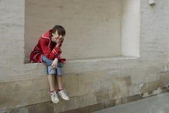 Retrato de la chica joven que se sienta en la pared Foto de archivo libre de regalías
