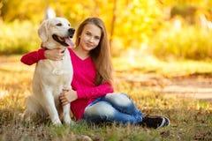 Retrato de la chica joven que se sienta en la tierra con su perro perdiguero del perro en escena del otoño Fotografía de archivo libre de regalías