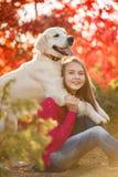 Retrato de la chica joven que se sienta en la tierra con su perro perdiguero del perro en escena del otoño Imagen de archivo