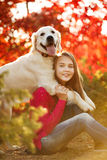 Retrato de la chica joven que se sienta en la tierra con su perro perdiguero del perro en escena del otoño Imágenes de archivo libres de regalías