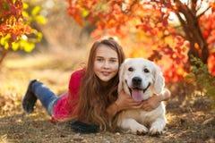 Retrato de la chica joven que se sienta en la tierra con su perro perdiguero del perro en escena del otoño Imagenes de archivo