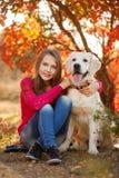Retrato de la chica joven que se sienta en la tierra con su perro perdiguero del perro en escena del otoño Fotografía de archivo