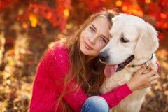 Retrato de la chica joven que se sienta en la tierra con su perro perdiguero del perro en escena del otoño Foto de archivo libre de regalías
