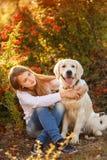 Retrato de la chica joven que se sienta en la tierra con su perro perdiguero del perro en escena del otoño Fotos de archivo