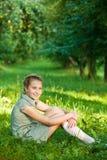 Retrato de la chica joven que se sienta en parque Foto de archivo libre de regalías