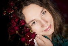 Retrato de la chica joven que sostiene las flores rojas Imágenes de archivo libres de regalías