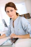 Retrato de la chica joven que trabaja con la tableta digital Foto de archivo
