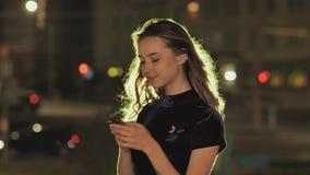 Retrato de la chica joven que usa el teléfono elegante y enviando los textos en ciudad de la noche almacen de metraje de vídeo