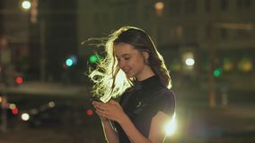 Retrato de la chica joven que usa el teléfono elegante y enviando los textos en ciudad de la noche almacen de video