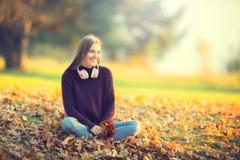 Retrato de la chica joven sonriente feliz con los auriculares en otoño Fotografía de archivo libre de regalías