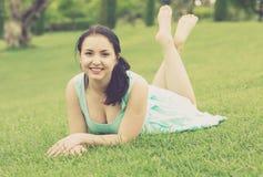 Retrato de la chica joven sonriente mientras que miente adentro al aire libre Imagen de archivo