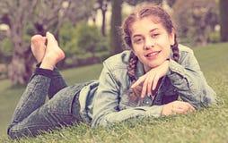 Retrato de la chica joven sonriente mientras que miente adentro al aire libre Fotografía de archivo libre de regalías