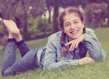 Retrato de la chica joven sonriente mientras que miente adentro al aire libre Fotografía de archivo