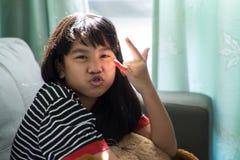Retrato de la chica joven tonta que hace caras divertidas Imagenes de archivo