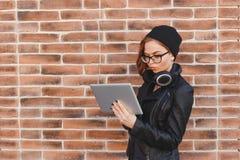 Retrato de la cintura de la mujer joven que se coloca en la calle al lado de la pared de ladrillo, música que escucha en línea co Imagen de archivo libre de regalías