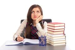 Retrato de la colegiala aburrida que hace su preparación en el escritorio Imagenes de archivo