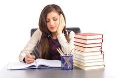 Retrato de la colegiala aburrida que hace su preparación en el escritorio Imagen de archivo libre de regalías