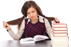 Retrato de la colegiala aburrida que hace su preparación en el escritorio Fotografía de archivo libre de regalías