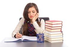 Retrato de la colegiala aburrida que hace su preparación en el escritorio Imagen de archivo