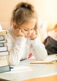 Retrato de la colegiala del trastorno que mira el libro de texto con la preparación Imágenes de archivo libres de regalías