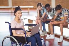 Retrato de la colegiala discapacitada que usa el ordenador portátil con los compañeros de clase en fondo Foto de archivo libre de regalías