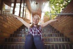 Retrato de la colegiala feliz que se sienta con los brazos extendidos en escalera Foto de archivo