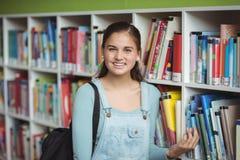 Retrato de la colegiala feliz que selecciona el libro en biblioteca Fotografía de archivo