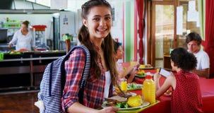 Retrato de la colegiala feliz que sostiene el desayuno en placa almacen de metraje de vídeo