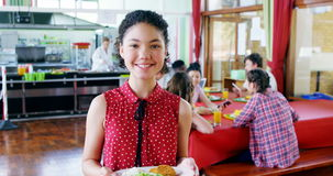 Retrato de la colegiala feliz que sostiene el desayuno en placa metrajes