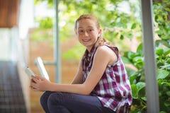 Retrato de la colegiala feliz que sostiene el teléfono móvil Fotografía de archivo libre de regalías