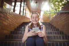 Retrato de la colegiala feliz que usa el teléfono móvil en escalera Fotografía de archivo