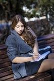 Retrato de la colegiala joven rubia que se sienta en el banco Fotos de archivo libres de regalías