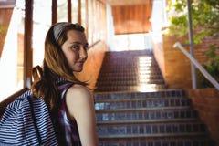 Retrato de la colegiala a la cartera que coloca la escalera cercana Fotografía de archivo libre de regalías