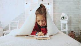 Retrato de la colegiala linda que lee un libro en pijamas, cubierto con la manta de lana blanca almacen de video