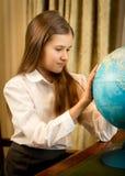 Retrato de la colegiala linda que mira el globo de la tierra Imágenes de archivo libres de regalías