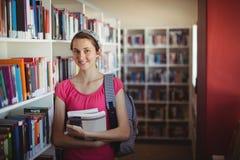 Retrato de la colegiala que se coloca con los libros en biblioteca Fotos de archivo libres de regalías