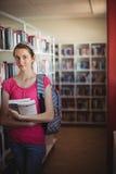 Retrato de la colegiala que se coloca con los libros en biblioteca Fotografía de archivo