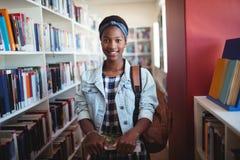 Retrato de la colegiala que se coloca con los libros en biblioteca Fotografía de archivo libre de regalías