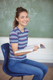 Retrato de la colegiala que se sienta en silla y que sostiene un libro en sala de clase Foto de archivo libre de regalías