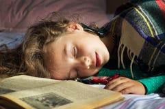 Retrato de la colegiala rizada joven que duerme en los libros Fotografía de archivo