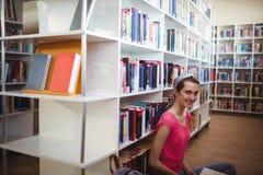 Retrato de la colegiala sonriente en biblioteca Fotografía de archivo