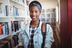 Retrato de la colegiala sonriente en biblioteca Imagen de archivo