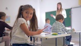 Retrato de la colegiala sonriente en el escritorio durante el aprendizaje de la lección en sala de clase en la escuela primaria e almacen de metraje de vídeo