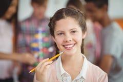 Retrato de la colegiala sonriente que se coloca con el lápiz en sala de clase Fotografía de archivo