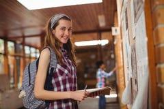 Retrato de la colegiala sonriente que se coloca con el libro cerca de tablón de anuncios en pasillo Foto de archivo
