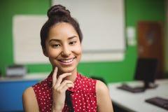Retrato de la colegiala sonriente que se coloca con la mano en la barbilla en sala de clase Imágenes de archivo libres de regalías