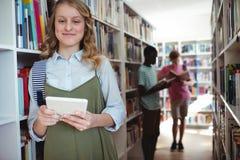 Retrato de la colegiala sonriente que se coloca con la tableta digital en biblioteca Imagenes de archivo