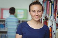 Retrato de la colegiala sonriente que sonríe en biblioteca Imagenes de archivo