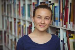 Retrato de la colegiala sonriente que sonríe en biblioteca Foto de archivo